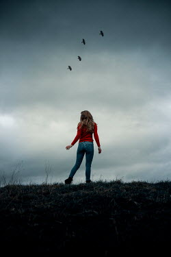 Rekha Garton Young woman in red sweater standing on hill