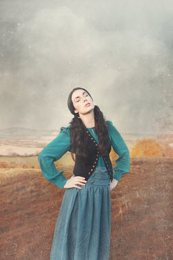 Anna Buczek Young woman in Victorian vest and dress standing on hill