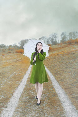 Anna Buczek Young woman in vintage green dress with umbrella in autumn