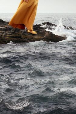 ILINA SIMEONOVA Legs of women in yellow dress standing on rocks by sea