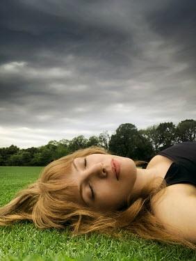 ILINA SIMEONOVA Young woman lying in grass