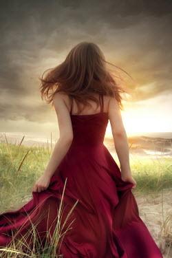 ILINA SIMEONOVA Young woman in red dress on sand dune