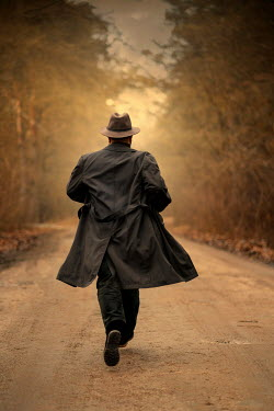 Jaroslaw Blaminsky Man in hat and coat running on rural road