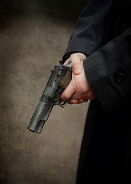 Jaroslaw Blaminsky Hands of man holding pistol