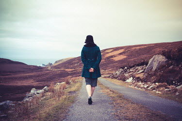 Marie Carr Woman with vintage coat walking on rural road