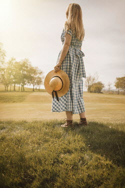 Shelley Richmond Young woman in vintage checked dress holding sun hat