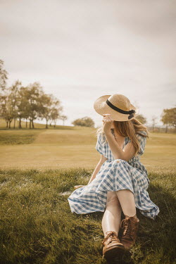 Shelley Richmond Young woman in vintage checked dress holding sun hat sitting in grass