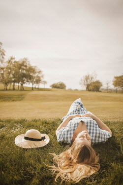 Shelley Richmond Young woman in vintage checked dress holding sun hat lying in grass