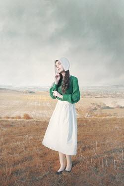 Anna Buczek WOMAN IN APRON AND BONNET STANDING IN COUNTRYSIDE Women