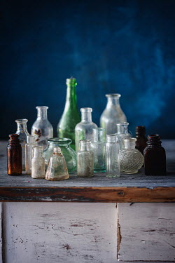 Magdalena Wasiczek antique glass bottles on wooden table Miscellaneous Objects