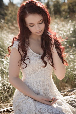 Michael Nelson GIRL WITH RED HAIR IN LACE DRESS SITTING OUTDOORS Women