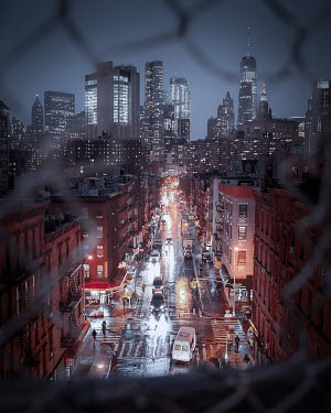 Paul Sheen STREET AND CITY SKYLINE AT NIGHT THROUGH WIRE FENCE Miscellaneous Cities/Towns