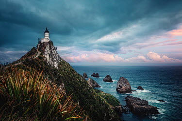 Evelina Kremsdorf LIGHTHOUSE ON CLIFF WITH ROCKS AND SEA AT SUNSET Miscellaneous Buildings