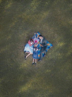Mary Wethey COUPLE WITH TWO DAUGHTERS ON RUG FROM ABOVE Groups/Crowds