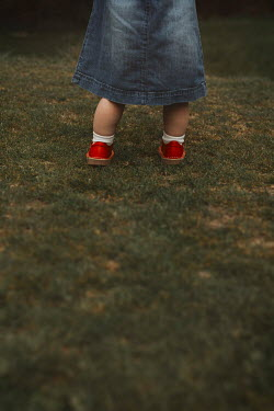 Shelley Richmond LITTLE GIRL WITH RED SHOES STANDING IN GARDEN Children