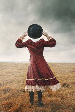 Anna Buczek GIRL WITH HAT IN STORMY COUNTRYSIDE FROM BEHIND Children