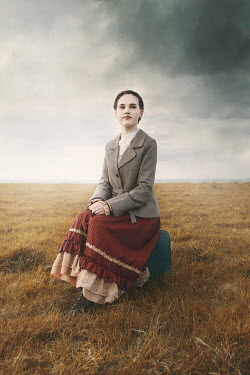Anna Buczek GIRL SITTING ON SUITCASE IN STORMY COUNTRYSIDE Children