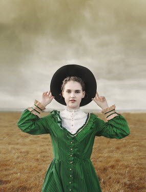 Anna Buczek GIRL HOLDING ONTO HAT IN COUNTRYSIDE Women