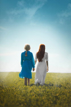Ildiko Neer Two women walking in field hand in hand
