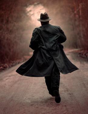 Jaroslaw Blaminsky MAN IN HAT AND COAT RUNNING ON COUNTRY ROAD Men