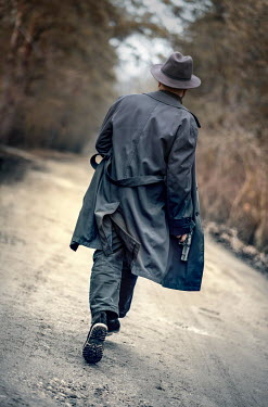 Jaroslaw Blaminsky MAN IN HAT WITH GUN WALKING ON COUNTRY ROAD Men
