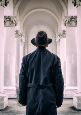 Jaroslaw Blaminsky MAN WITH HAT STANDING IN CORRIDOR WITH PILLARS Men