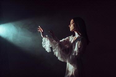 Ulyana Naydenkova WOMAN WITH RAISED HANDS IN LIGHT WITH SMOKE Women