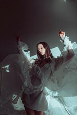 Ulyana Naydenkova WOMAN WITH RAISED ARMS IN WHITE FLOWING DRESS Women