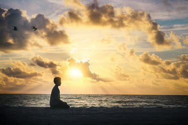Evelina Kremsdorf Boy sitting on beach at sunset