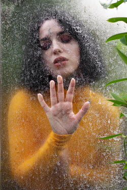 Holly Leedham Young woman in yellow sweater behind window