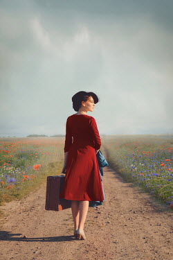 Joanna Czogala Woman in red dress with suitcase on country road