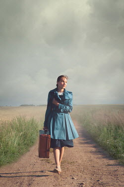 Joanna Czogala Young woman with suitcase on country road