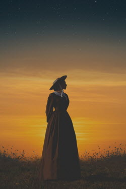 Joanna Czogala Young woman in brown dress and straw hat at sunset