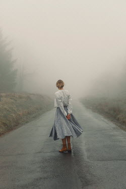 Rekha Garton Young woman standing on road in fog