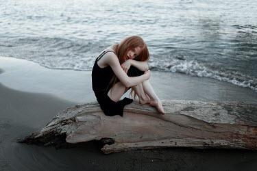 Ulyana Naydenkova Young woman sitting on log at beach