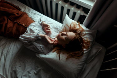 Ulyana Naydenkova Young woman lying on bed from above