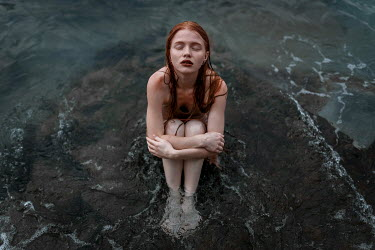 Ulyana Naydenkova Young woman sitting on rock in sea