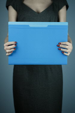 Magdalena Russocka close up of woman holding file folder