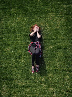 Elisabeth Ansley Sad teenage girl lying in grass from above