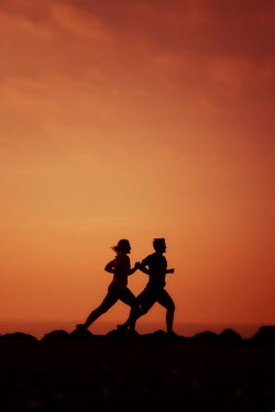 Tim Robinson Silhouette of couple running at sunset
