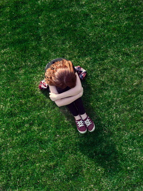 Elisabeth Ansley Sad teenage girl sitting in grass from above