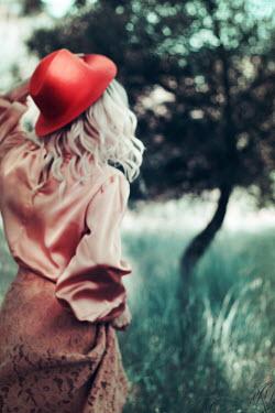 Irene Lamprakou Young woman in hat walking in field