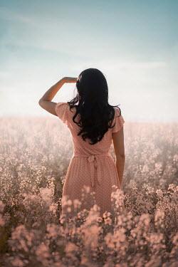 Ildiko Neer Black hair woman standing in flower field