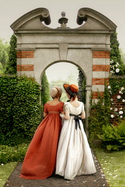ILINA SIMEONOVA Young women in regency dresses walking to garden archway