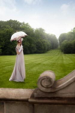 ILINA SIMEONOVA Young woman with parasol on lawn