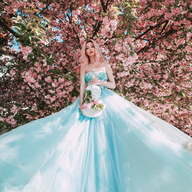 Jovana Rikalo Young woman in blue gown under cherry blossom tree