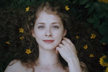 Irina Orwald GIRL LYING IN FIELD WITH YELLOW FLOWERS Women