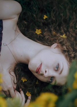 Irina Orwald GIRL LYING ON GROUND WITH YELLOW FLOWERS Women