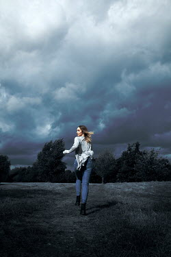 Miguel Sobreira WOMAN RUNNING IN STORMY COUNTRYSIDE FROM BEHIND Women