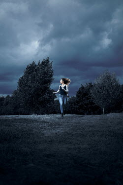 Miguel Sobreira WOMAN RUNNING IN STORMY COUNTRYSIDE AT DUSK Women